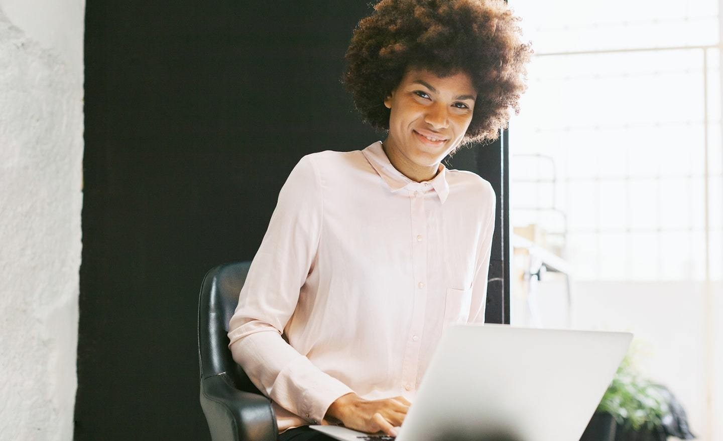 Black woman in chair with laptop