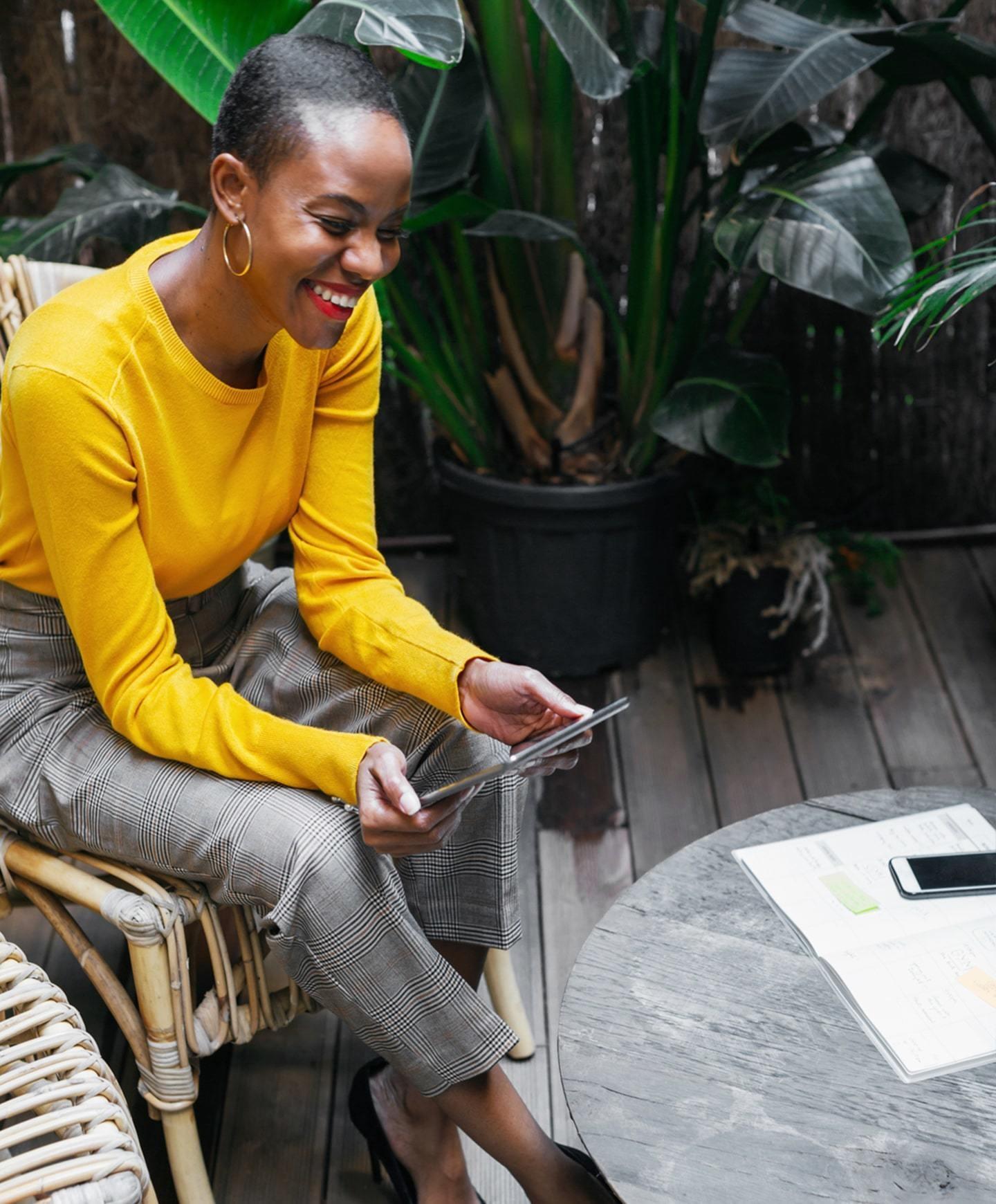 一个黑人妇女坐在户外的一张桌子旁