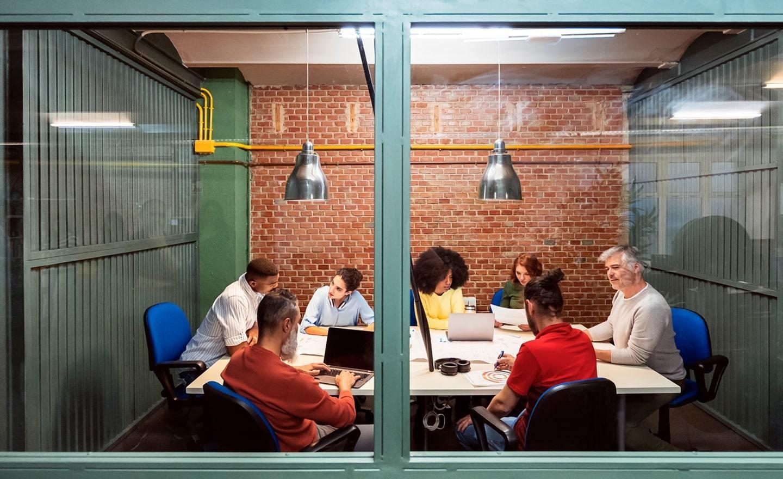 Coworkers meeting seen through glass window