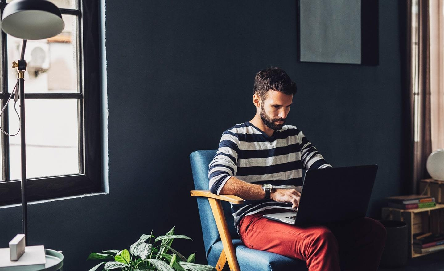 Man in red pants working on laptop