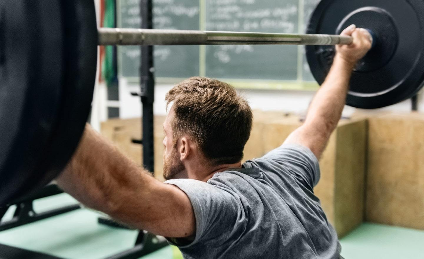 Man lifting weights seen from behind