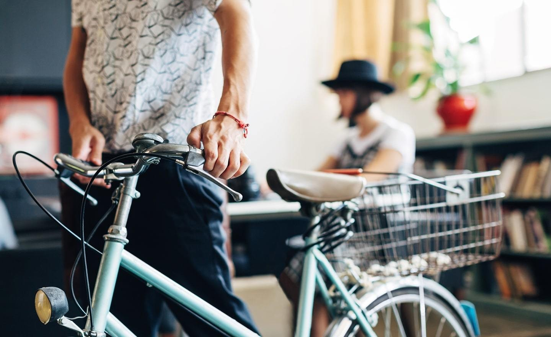 Man walking a bike through an office space