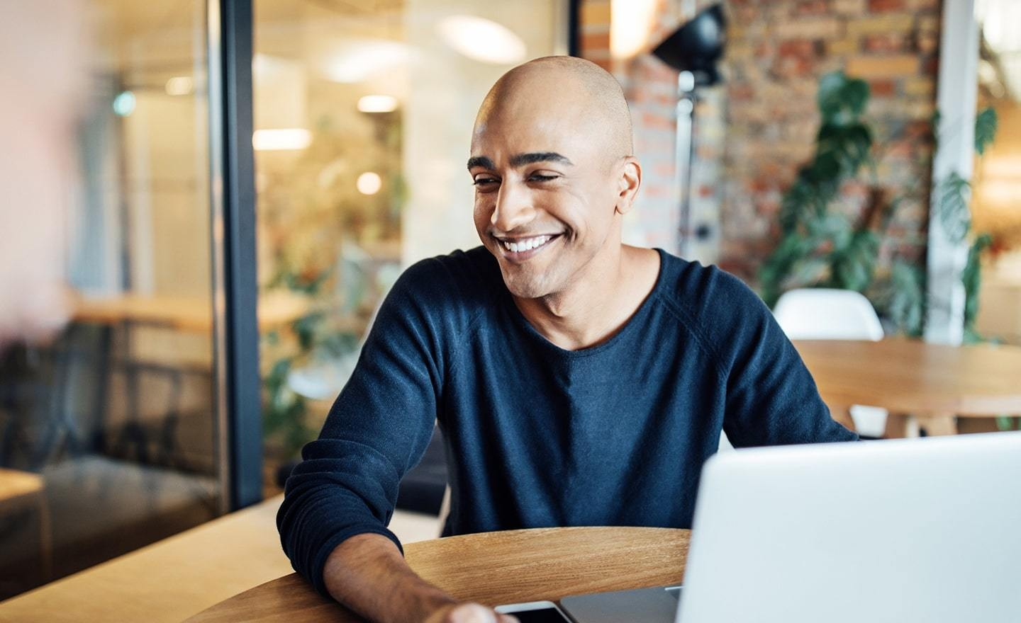 Man with shaved head smiling in front of a laptop