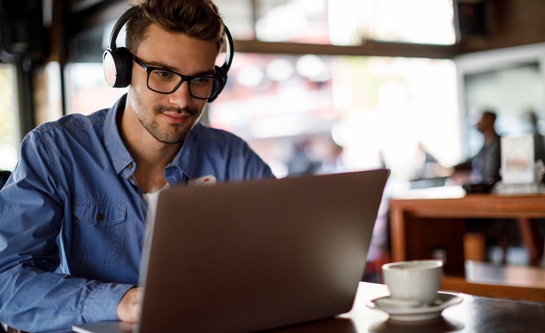 一个戴着耳机在咖啡店工作的男人
