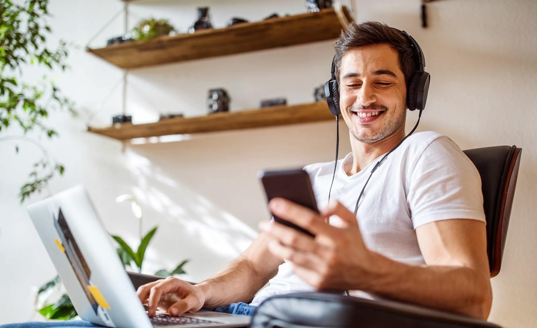 Man working on laptop checking phone