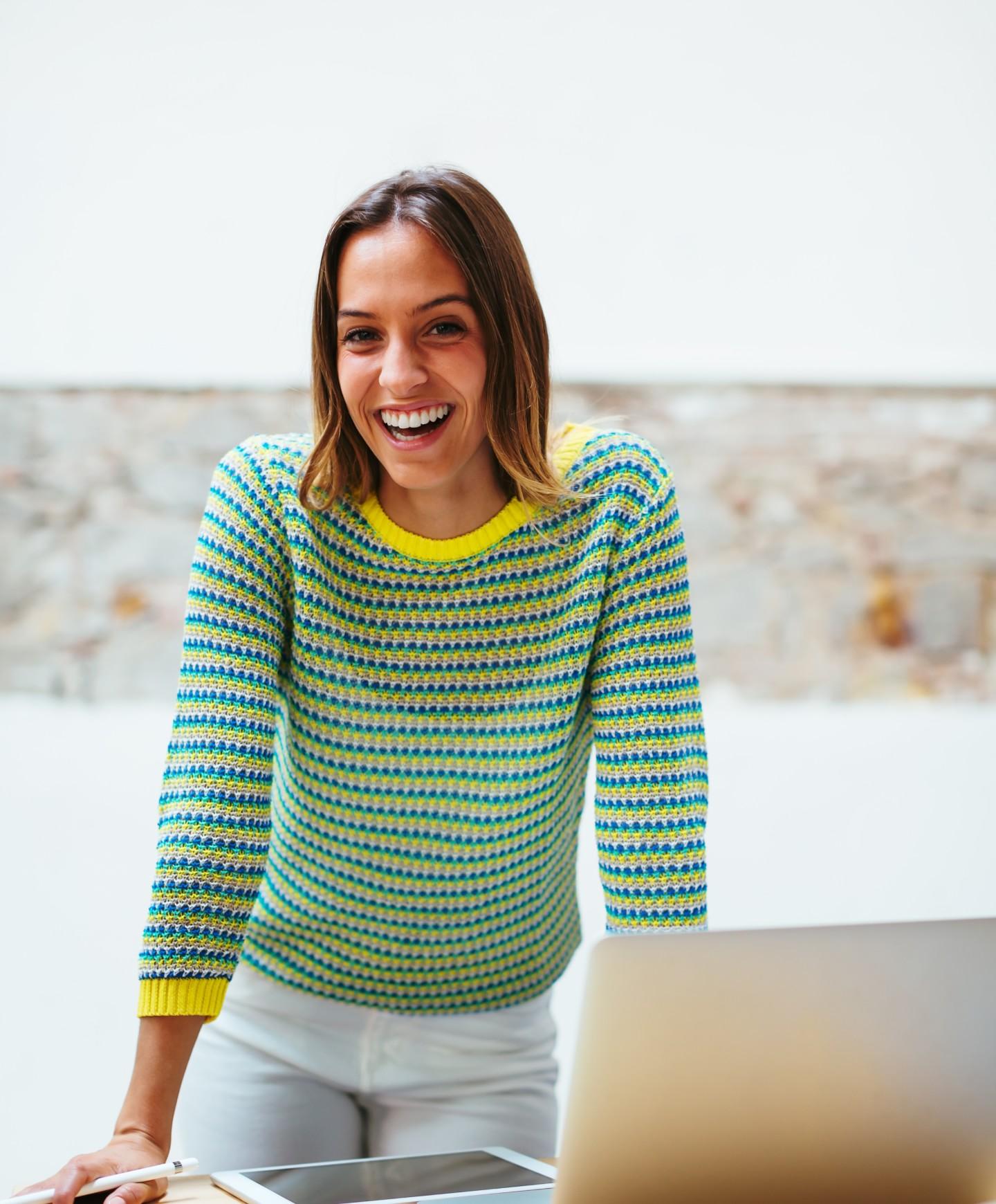 一张穿着条纹毛衣的微笑女人的照片