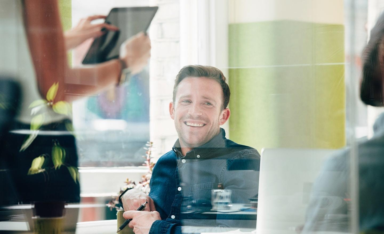 Smiling man seen through a window
