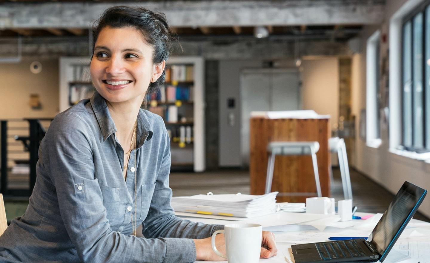 Smiling woman at desk with laptop