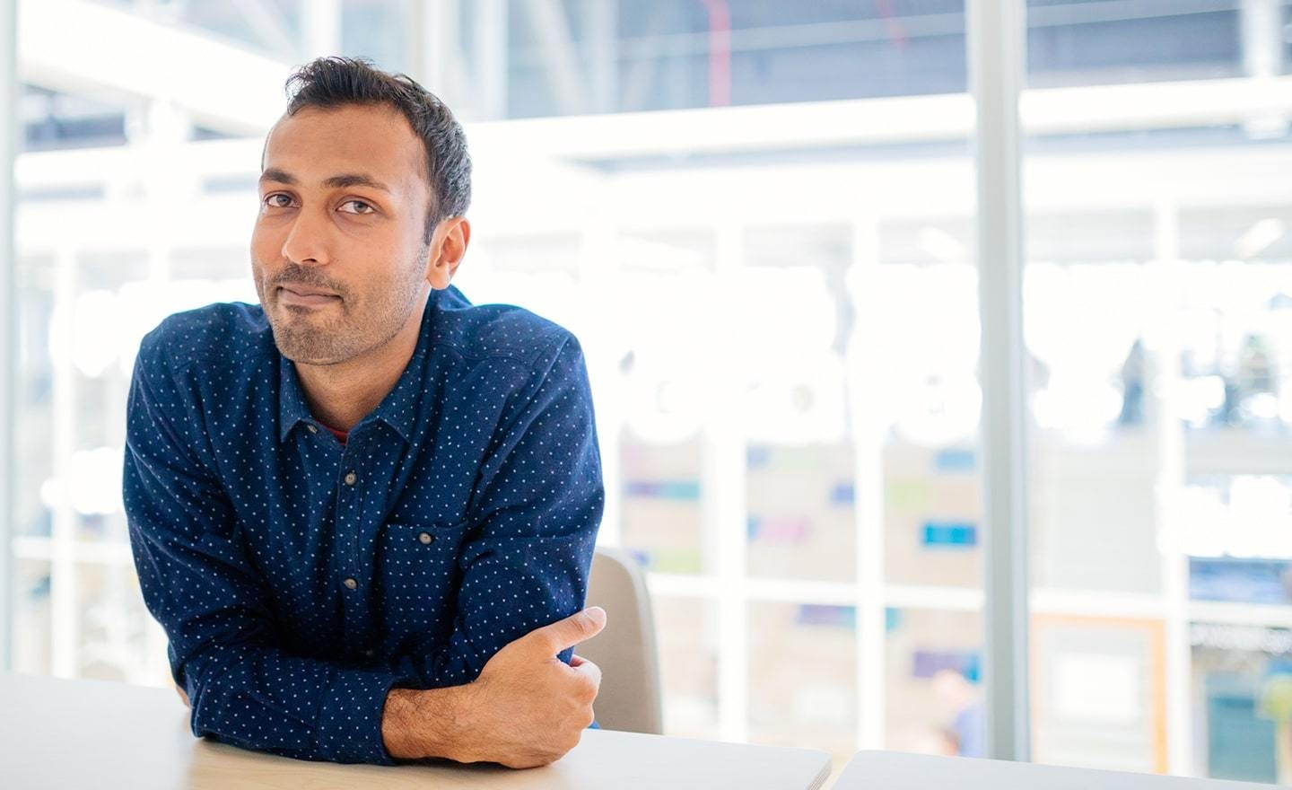 South Asian man with crossed arms in a conference room