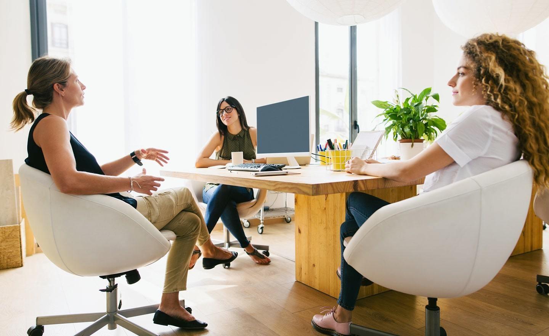 Three women gathered around a desk