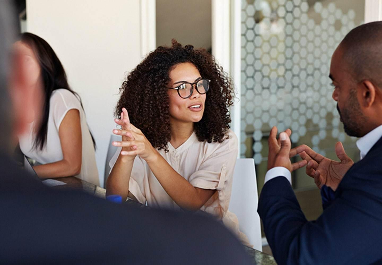 Two people of color speaking in meeting
