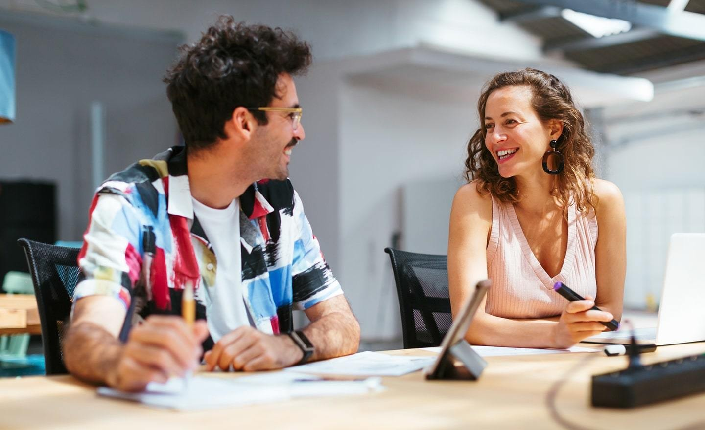 Two people smiling and talking seated at a desk