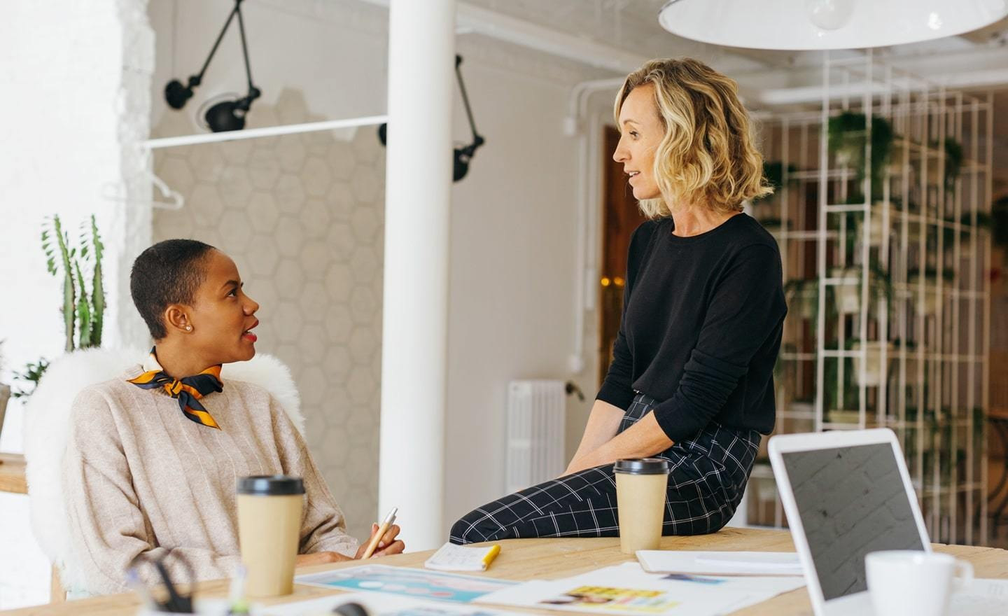 Two women coworkers in conversation at a desk