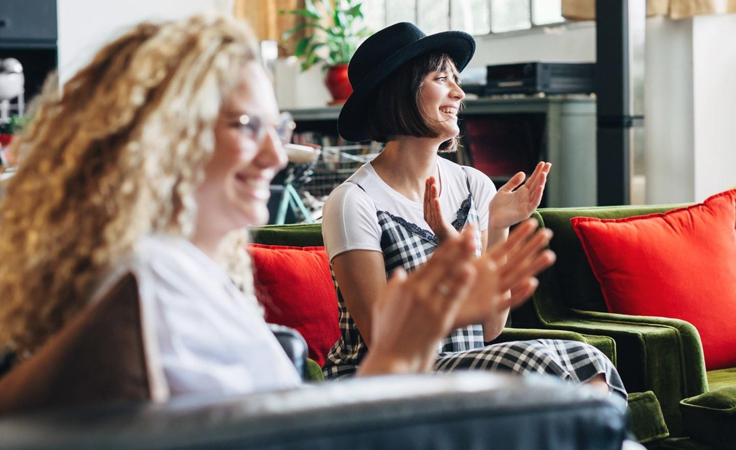 Two women sitting on couch clapping