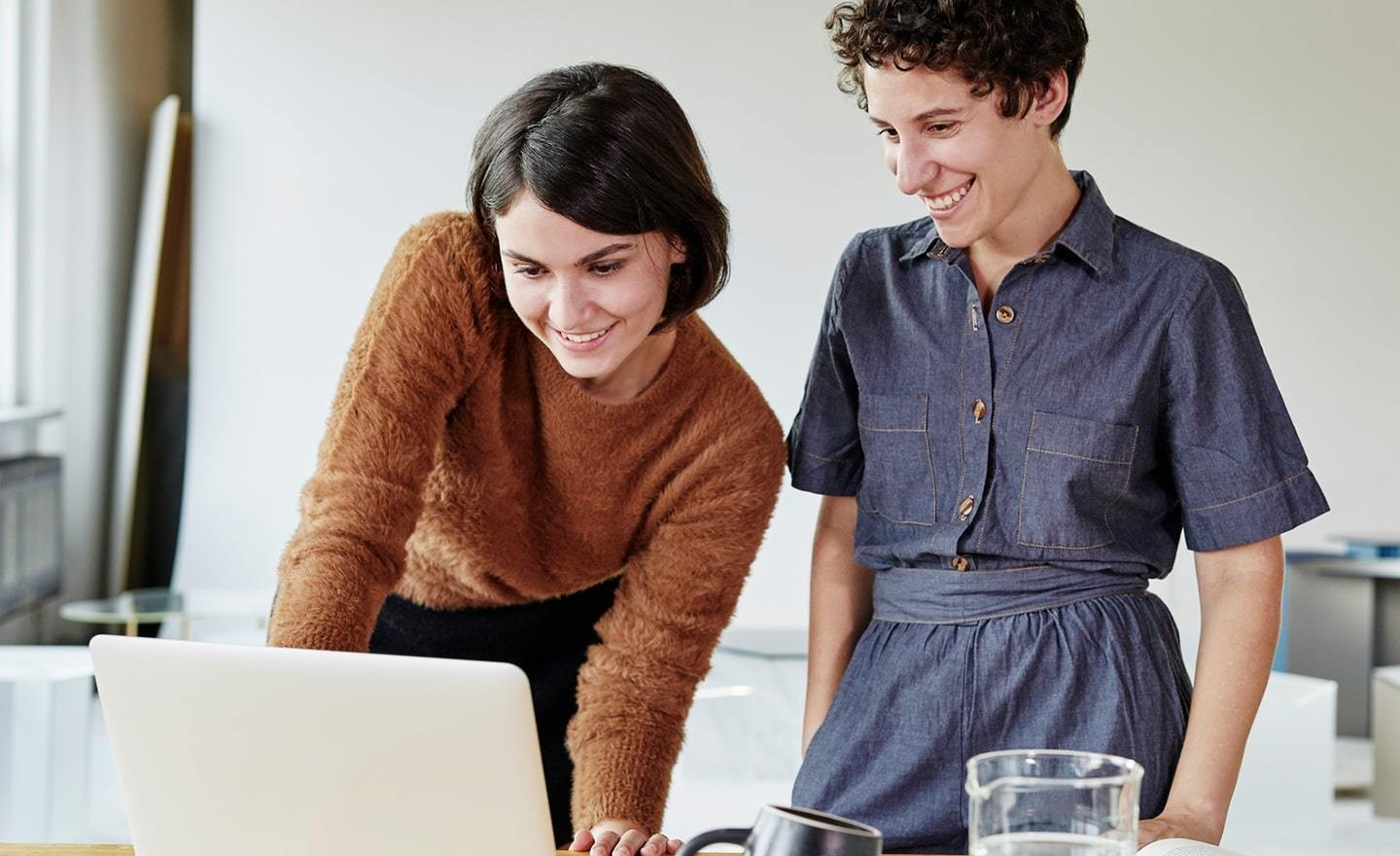 Two women standing over laptop
