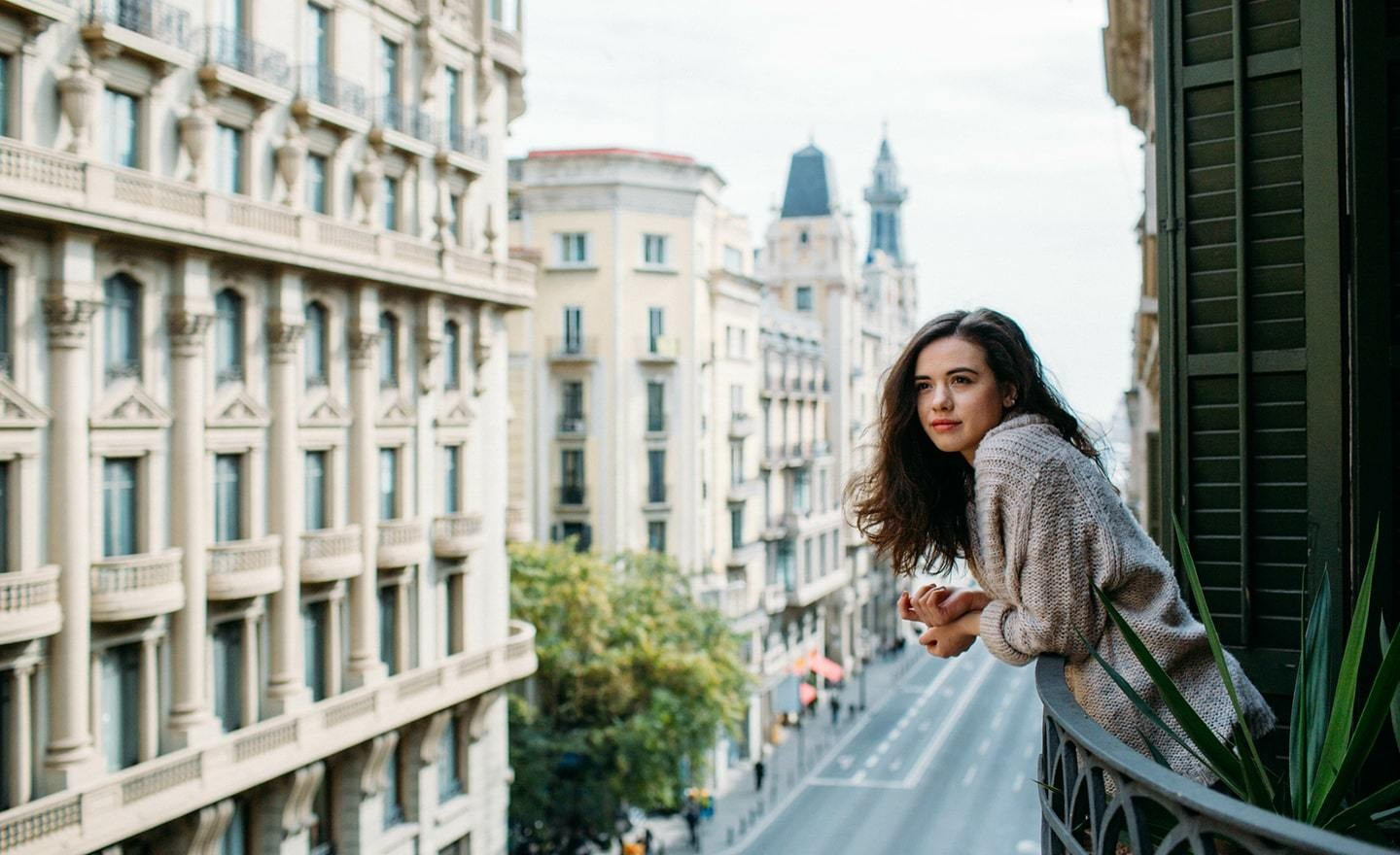 Woman looking out a balcony in a European city