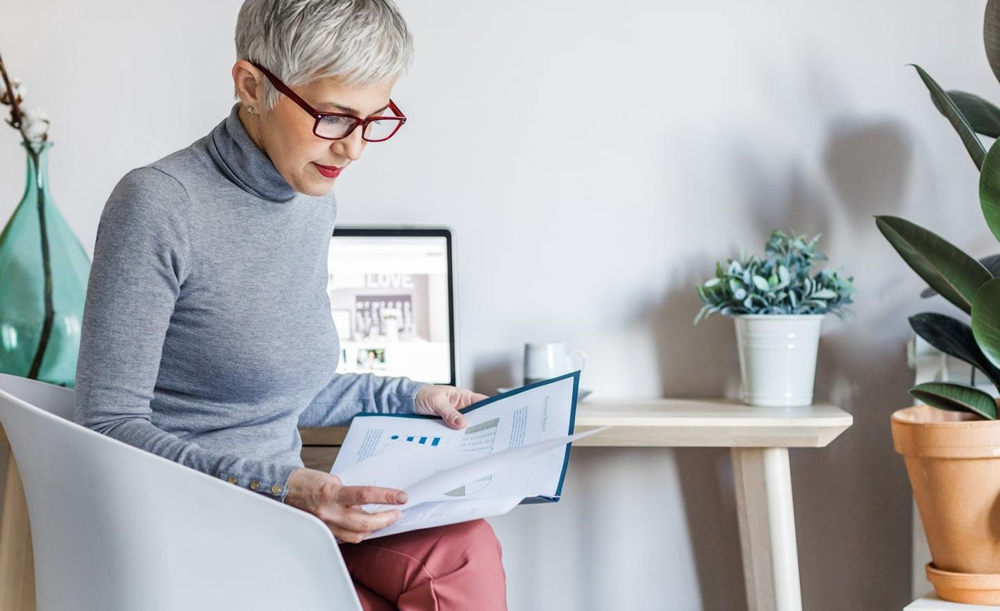 Woman with gray hair reading report at her desk