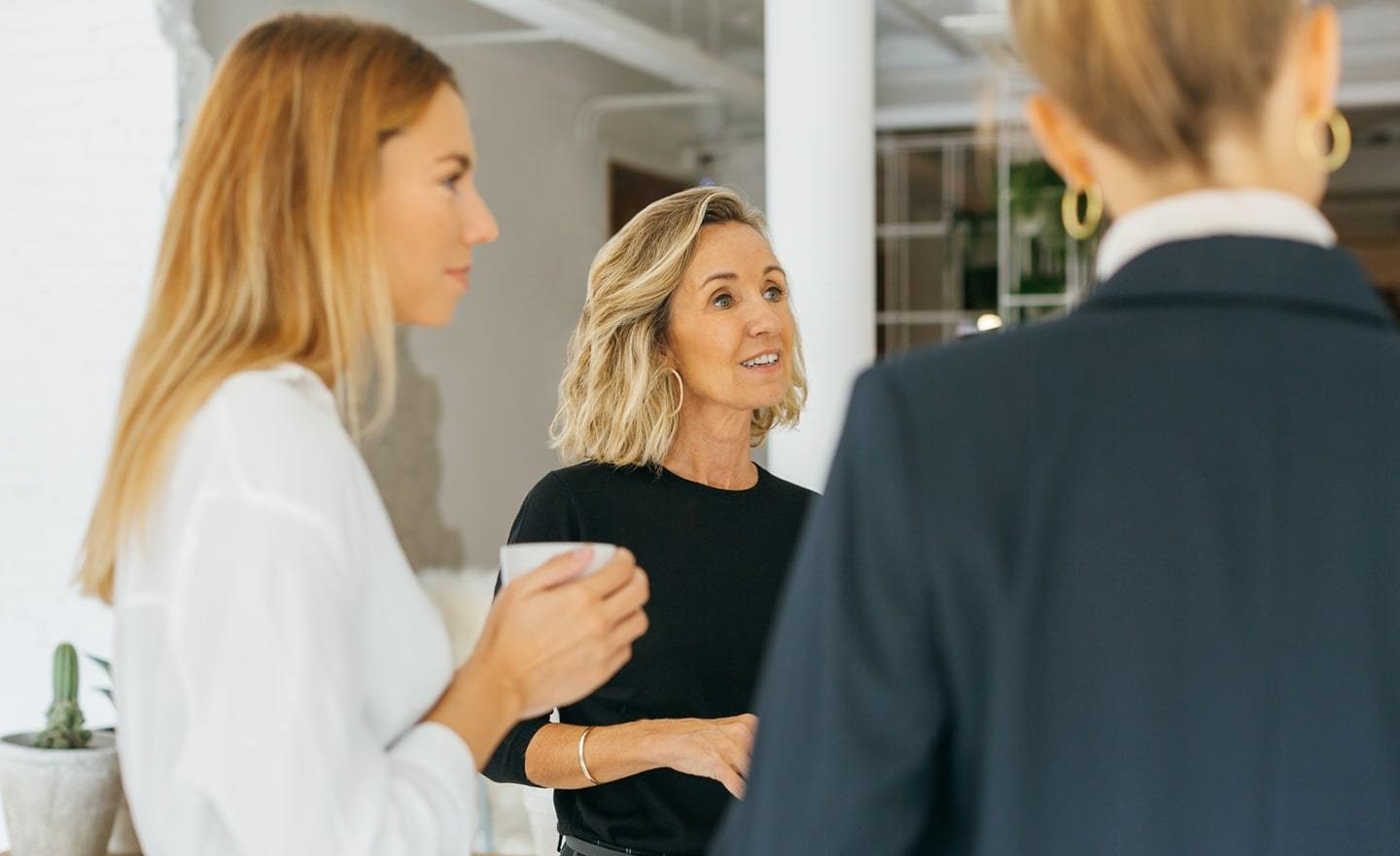 Women standing in a group having a conversation