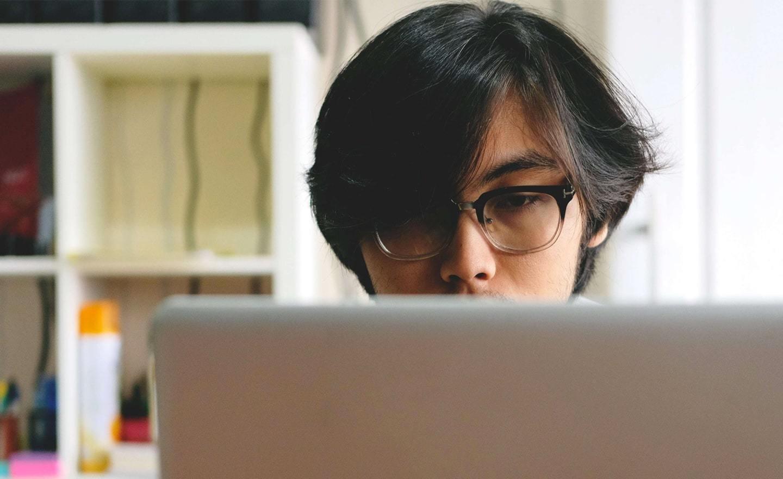 Young Asian man at a laptop