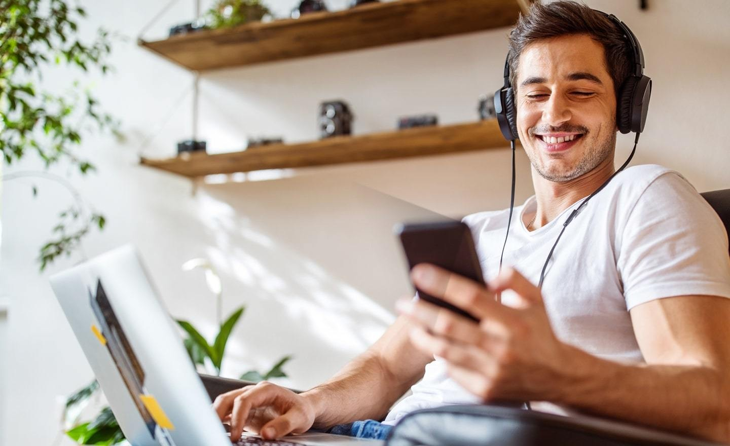 Young man in lounge chair wearing headphones