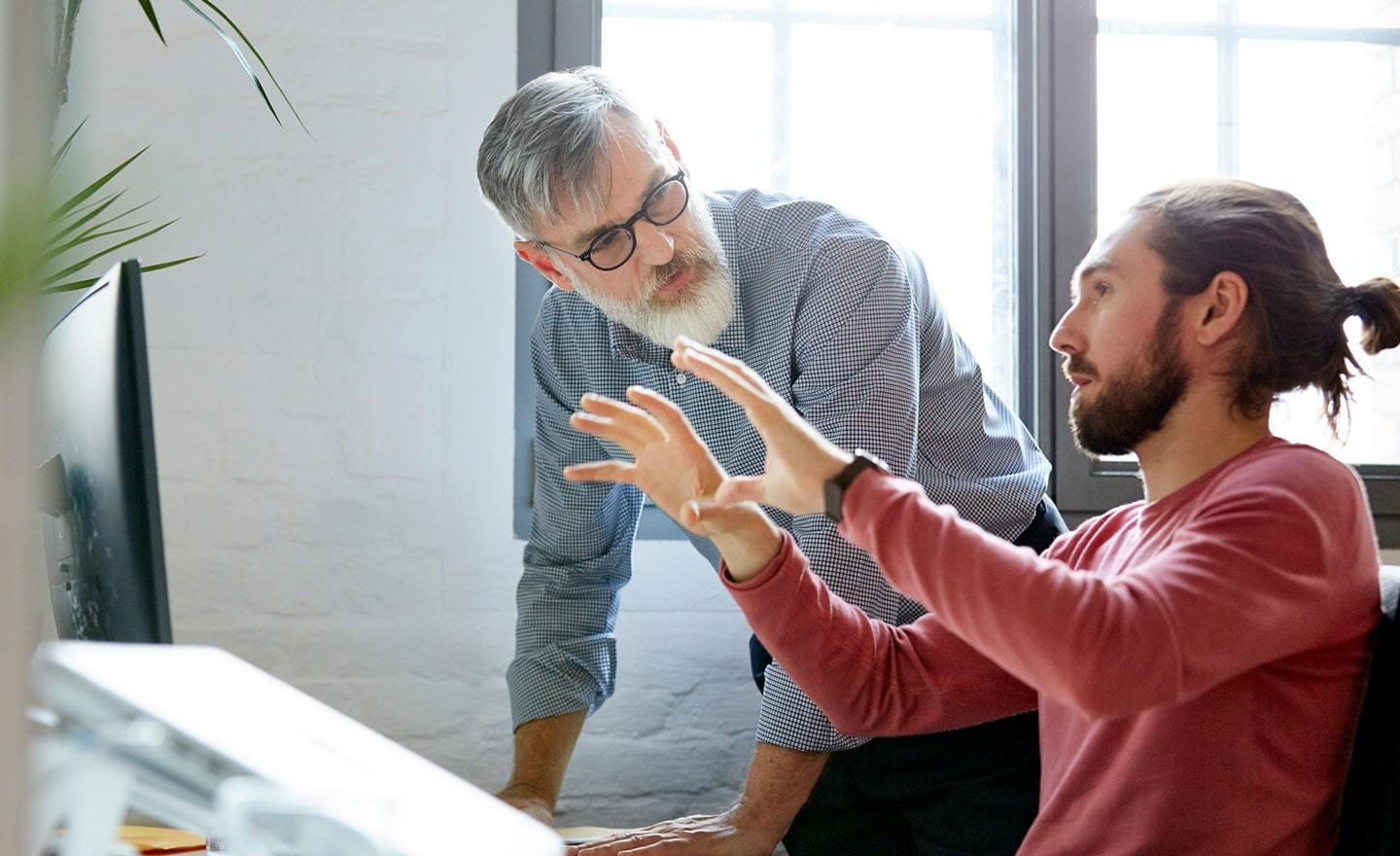 Young man presenting work to boss at desk
