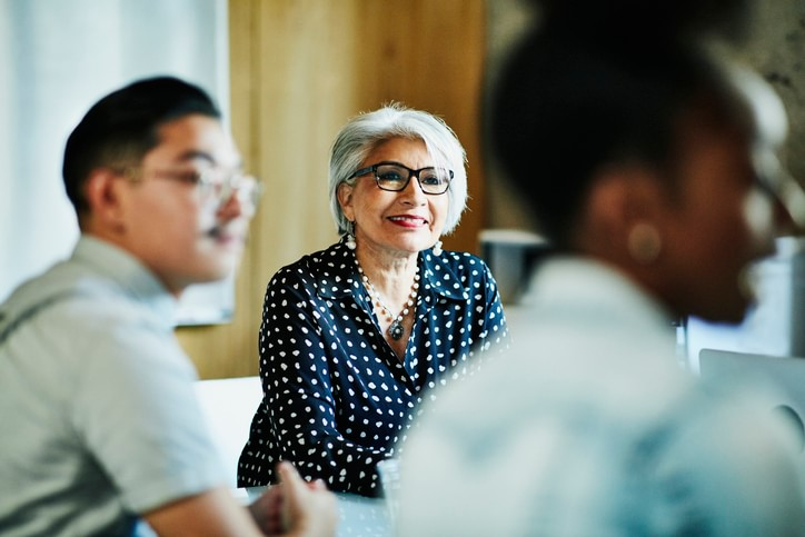 Photo of a woman looking on in a group meeting