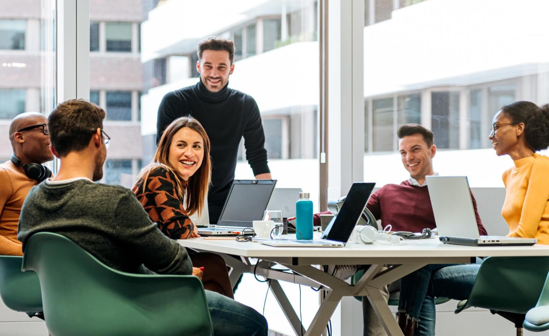 公司办公室里一群同事围坐在会议桌旁