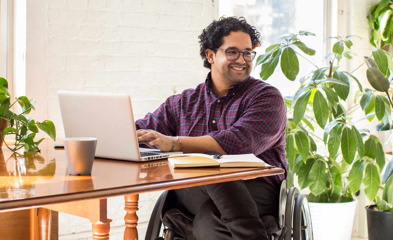 Man in wheelchair working on laptop
