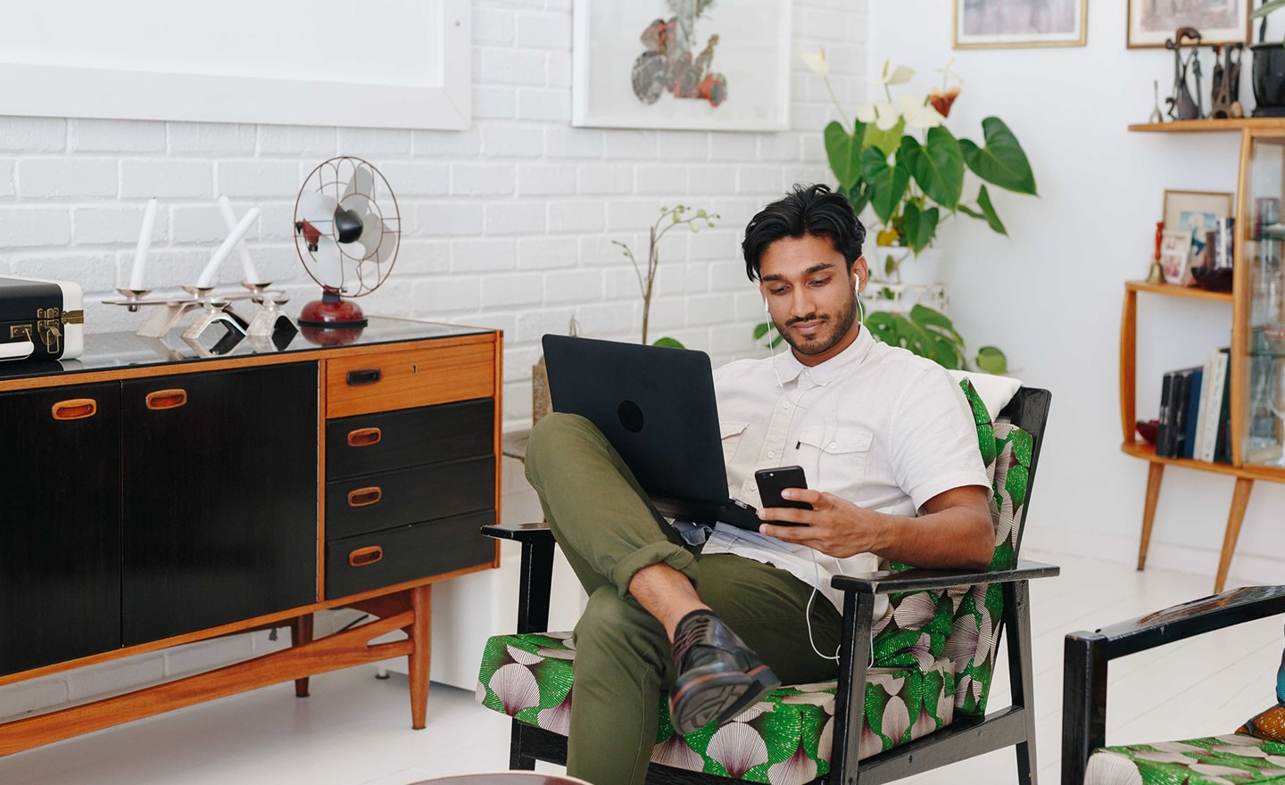 Man working at home on phone and laptop