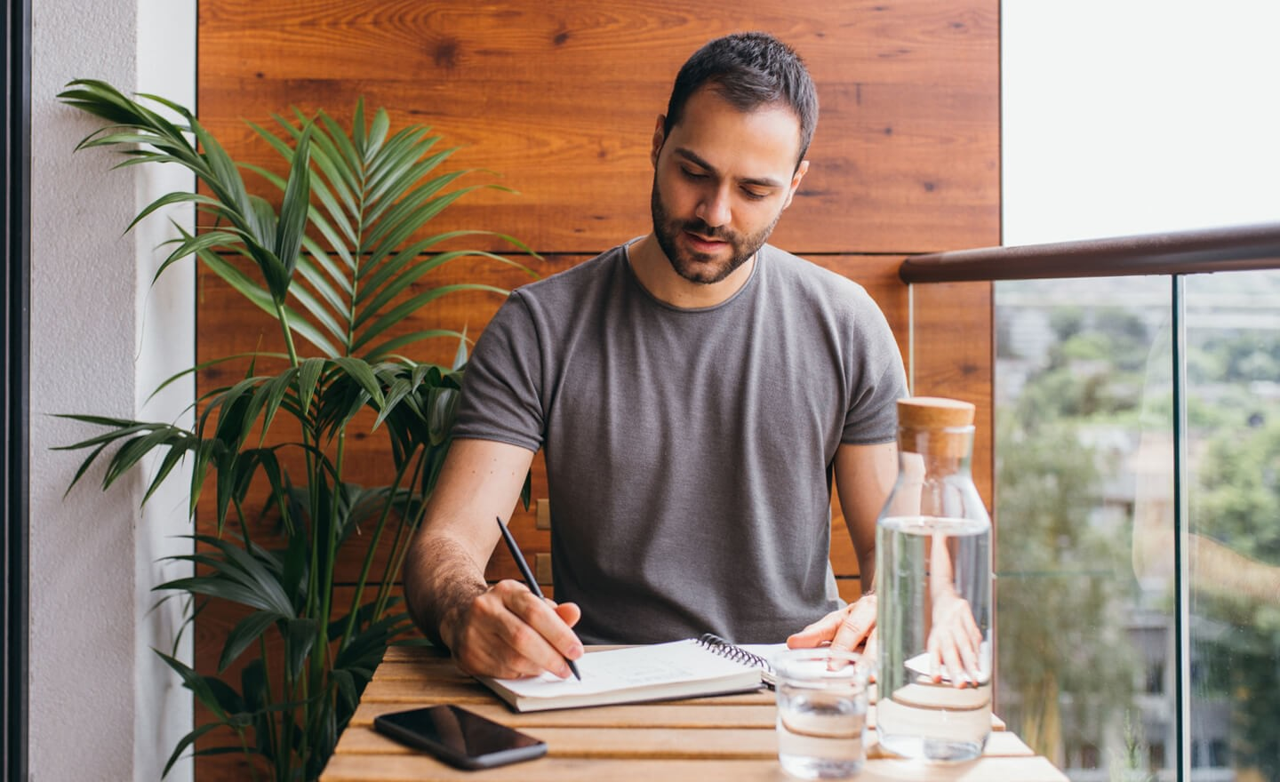 Man writing in notebook at outdoor home desk
