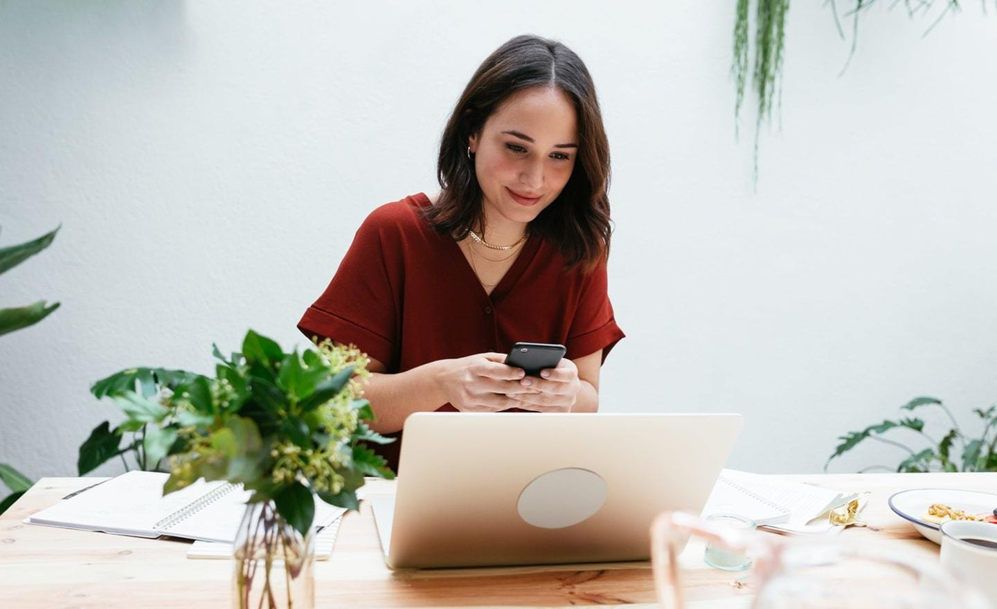Woman working on laptop and phone