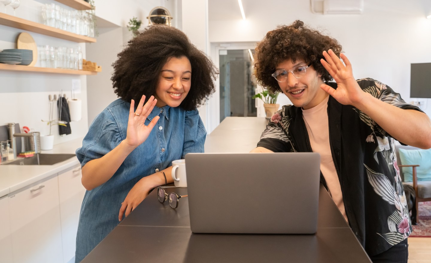 Man and woman attending video call waving