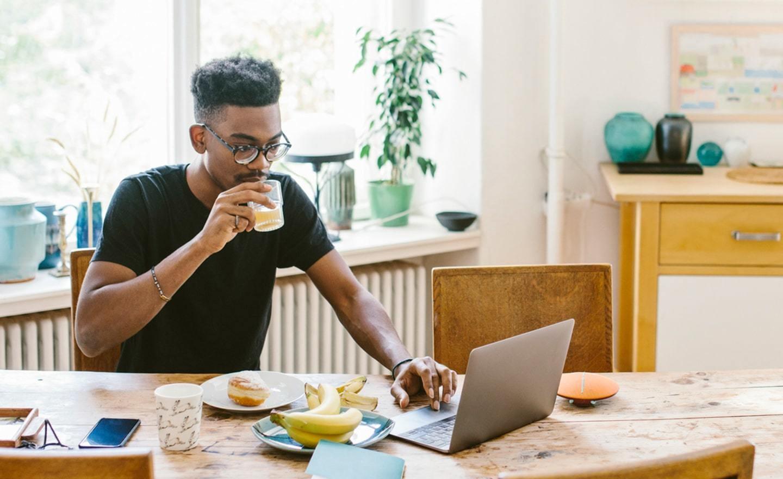 Man working on laptop in kitchen
