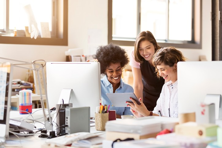 Three women in an office smiling