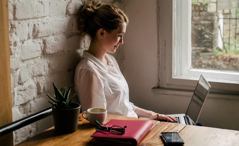 坐在窗边用笔记本电脑的女人